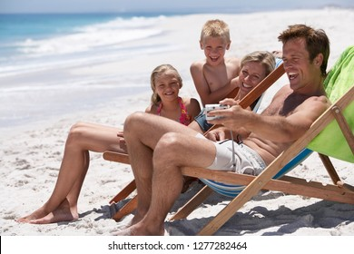 Family in deckchairs on sandy summer vacation beach in swimwear as father takes selfie with camera