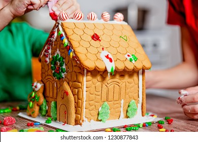 family decorates gingerbread house. the concept of family preparing to Christmas. selective focus