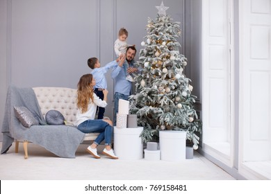 Family Decorating a Christmas Tree. Family Decorates the spruce in the Living Room with Toys and a herring, Joyful Children Help the Parents