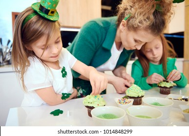 Family decorating cupcake at kitchen