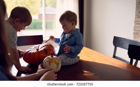 Family decorating pumpkins together for Halloween