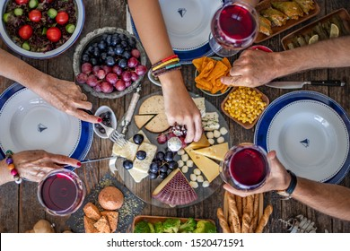 Family dinner for a celebration with red wine and cheers. Top view of a family dinner (meal) with togetherness