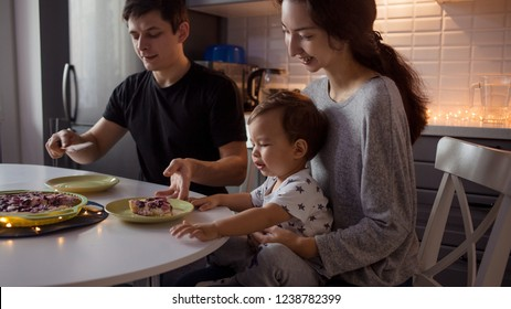 Family dinner, Father mom and baby at home in the kitchen. Happy multi-ethnic family and a festive dinner in a cozy kitchen