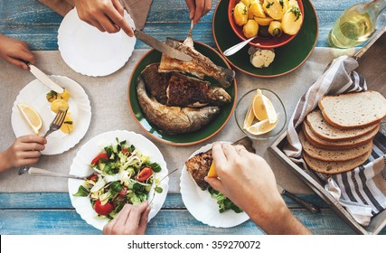 Family dinner with fried fish, potato and salad