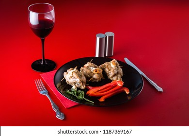 Family dinner. Meat dish with paprika and salad on a black plate with a glass of wine on a red background