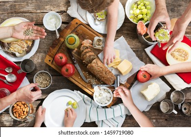 Family dinner table top view with hands holding and eating food. Healthy organic food sandwiches and snacks. Fresh bread tomatoes seeds cream cottage cheese on tray, plates