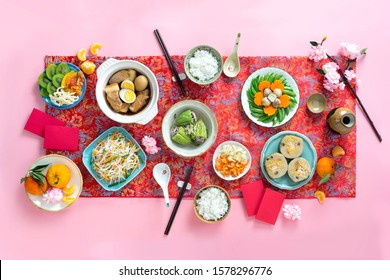 Family dinning table of Tet holiday or Lunar New Year with traditional foods: pork belly and eggs braised in coconut water, pickles, rice, Banh Tet (rice cake), fried vegetables, bitter melon soup
