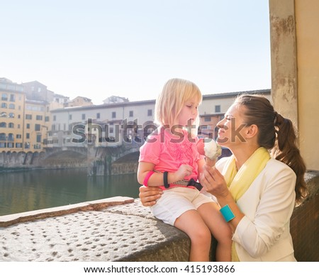 Family discovering old Italian treasures in Florence. Happy mother and daughter eating ice cream near Ponte Vecchio
