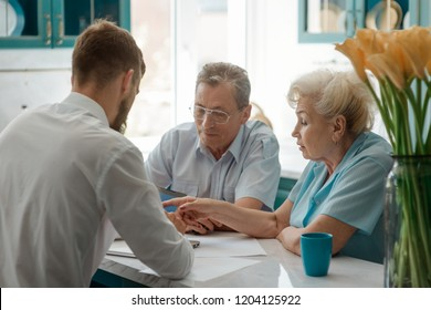 Family discussing about finances over a cup of tea at their kitchen. Senior couple and adult son.