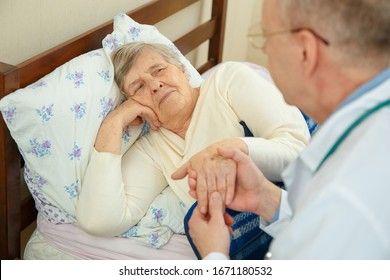 The family doctor communicates with a sick elderly woman. Home doctor discusses the condition of a sick woman