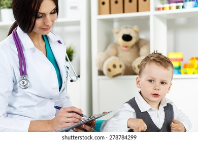 Family doctor examination. Little child visiting pediatrician. Beautiful female medical doctor with freckles communicating with cute young patient. Paediatrics medical concept