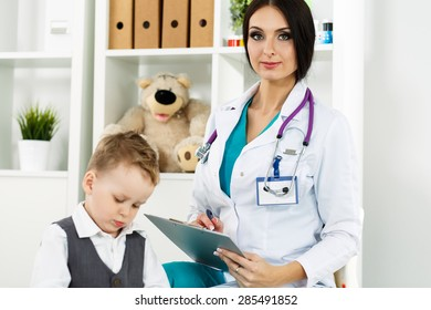 Family doctor examination. Little child visiting pediatrician playing. Beautiful female medical doctor with freckles communicating with cute young patient. Paediatrics medical concept