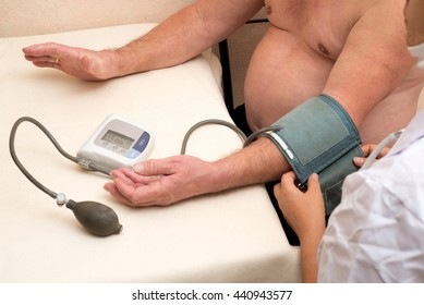 Family doctor measures the blood pressure of an elderly patient at home