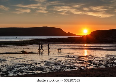 A family with dog in silhouette walking on a beach at Daymer Bay in Cornwall England.  The setting sun is reflecting on the wet sand and the sea in the Camel estuary.