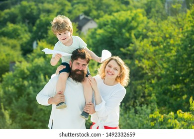 Family dreams of traveling. Father mother and his son playing outdoors. Cute little boy is holding paper airplane. Father carrying his son on shoulders