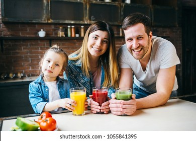 Family drink juice in the kitchen. Health care concept.