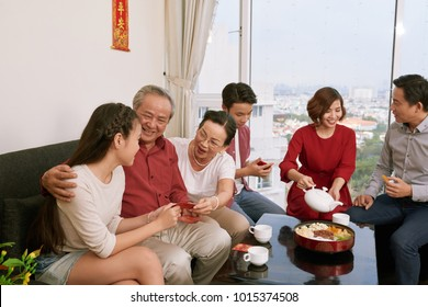 Family drinking tea and giving traditional lucky money envelopes to children at Tet celebration