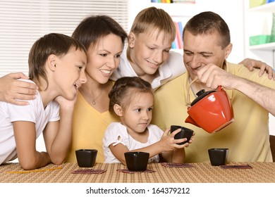 Family drinking tea at table in kitchen