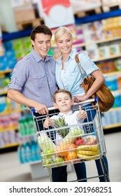 Family drives cart with food and boy sitting there. Concept of fresh and healthy food and consumerism