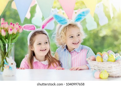 Family Easter morning. Children dye eggs. Kids with bunny ears search for candy and chocolate eggs on Easter egg hunt. Home decoration with tulip flowers, pastel rabbit banner and dye egg basket