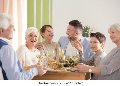 Family eating easter dinner, sitting together beside table