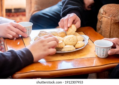 Family eating Eid sweets and drinking Arabic coffee