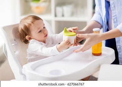family, eating, feeding and people concept - mother giving spout cup with juice to baby at home