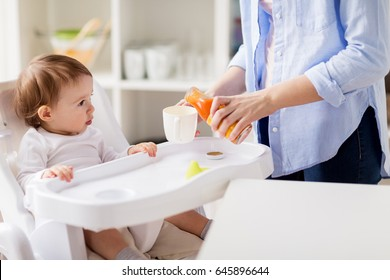family, eating, feeding and people concept - little baby and mother pouring natural carrot juice from glass bottle to cup at home kitchen