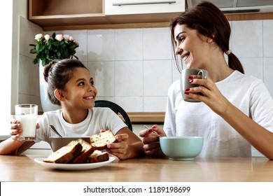 Family. Eating. Home. Mom and daughter are talking and smiling while having lunch in the kitchen at home