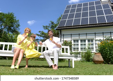 Family eating iced lollies in garden of solar paneled house