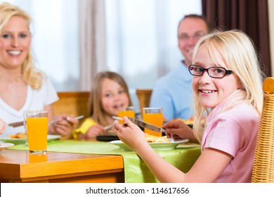 Family eating lunch or dinner and sitting at the table