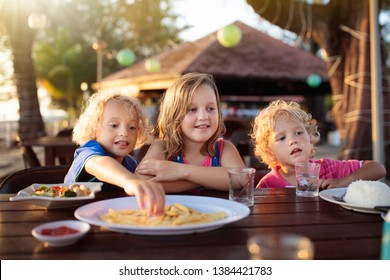 Family eating lunch on tropical beach. Kids in outdoor restaurant of exotic resort in Asia. Asian food for children. Little boy and girl eat dinner at sea coast. Holiday with child.