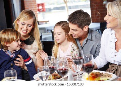Family eating lunch with their children and the grandmother