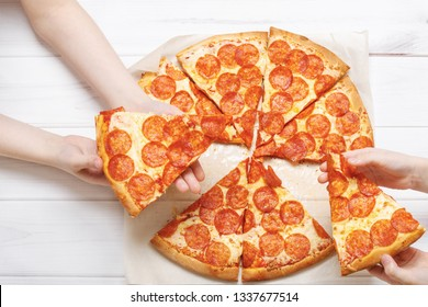 Family eating peperoni pizza. Kids holding a slice of pizza.