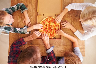 Family eating pizza together, overhead view