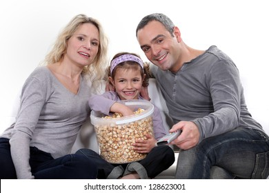 Family eating popcorn on a sofa