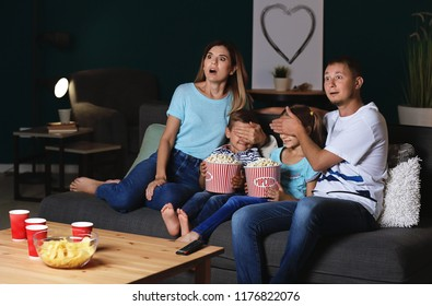 Family eating popcorn while watching scary movie in evening
