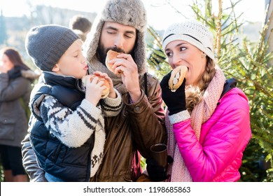 Family eating rolls and sausage on Christmas Market in front of tree