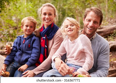 Family eating sandwiches outdoors in a forest, portrait