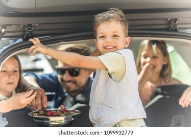 Family Eating Strawberries in a Car Trunk, focus on a boy