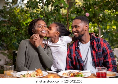 A family eating together, daughter kissing mother on the cheek