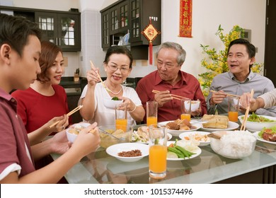 Family eating various traditional dishes at Tet celebration. Scrolls wishing luck and wealth in the background