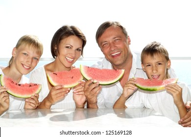 family eating watermelon in the background of the sea