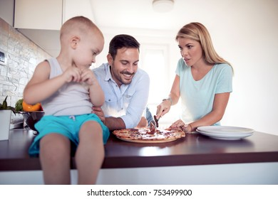 Family eating yummy pizza together in kitchen.