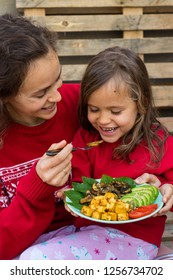 Family eats buddha bowl for Christmas lunch, dinner. Young woman (mother), little girl (daughter). Fried tofu, avocado slices, mushrooms, tomatoes, spinach. Healthy vegetarian food. Red jackets