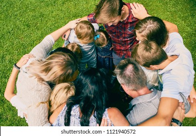 Family of eleven standing embracing in circle