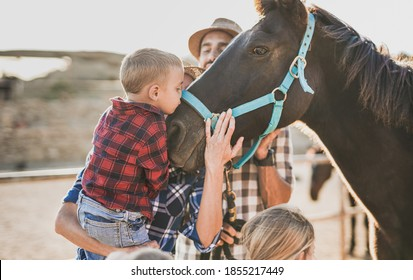 Family enjoy day at horse ranch - Little boy kiss a horse - Parents, children and animal love