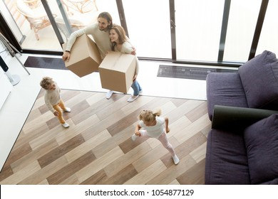 Family enjoy luxury house on moving day, happy parents holding boxes excited by big modern living room coming into new home while kids children playing together, mortgage relocation concept, top view