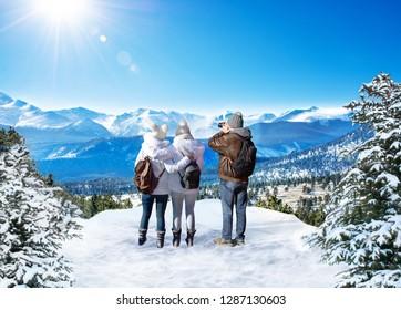 Family enjoying beautiful  mountain view on winter  hiking trip. People on winter vacation. Rocky Mountain National Park. Close to Estes Park, Colorado, USA