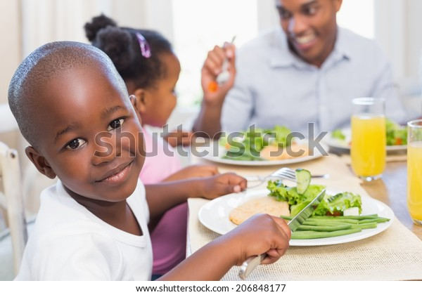 Family enjoying a healthy meal together with son smiling at camera at home in the kitchen